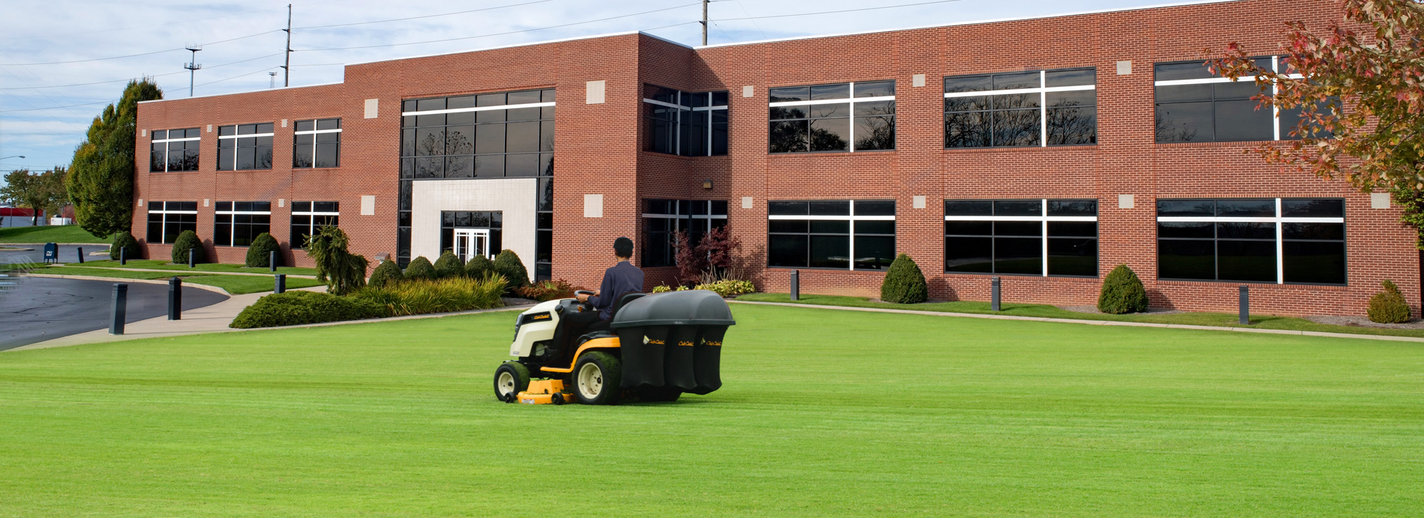 A man mowing a lawn on a commercial property